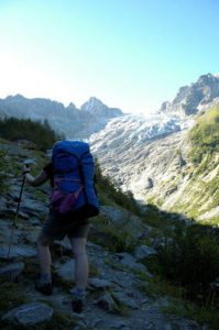 Woman walking in the Swiss Alps with a Berghaus Cyclops blue rucksack and a pink Shock Absorber B4490 sports bra hanging on the back