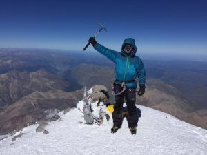 Michael Goude owner of RockRiver Expeditions stood on the summit of Mt Elbrus in Russia holding his walking axe above his head in celebration