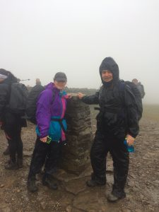 Two walkers at the trig point at top of Pen-y-Ghent in the mist and rain