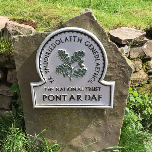 The marker stone for Pont Ar Daf showing the National Trust logo and the text Yr Ymddiriedolaeth Genedlaethol (The National Trust in Welsh)
