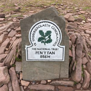 The summit stone at the top of Pen-y-Fan showing the National Trust logo of the oak leaf and the height of the summit 886m