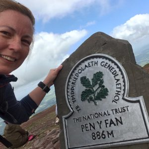 The summit stone at the top of Pen y Fan, detailing the National Trust logo and the summit height 886m. Paula Goude from RockRiver Expeditions is also in the photograph.