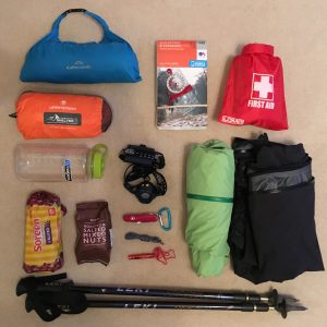 12 items needed in your rucksack for a day walk in the UK. Including waterproof jacket and trousers, walking poles, food and drink, whistle, pen knife, spare laces, warm jacket, map and compass, waterproof bags, a first aid kit and an emergency shelter