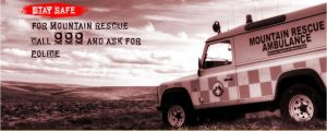 Mountain Rescue poster showing a Mountain Rescue Ambulance overlooking a wide expanse of countryside, and the words Stay Safe. For Mountain Rescue call 999 and ask for Police