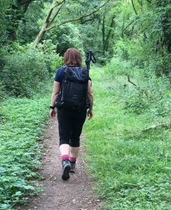 Paula Goude from RockRiver Expeditions walking through the woods with a black Osprey rucksack