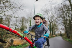 Child riding on a bike wearing the Lukla merino wool baselayer from Amamaya Clothing