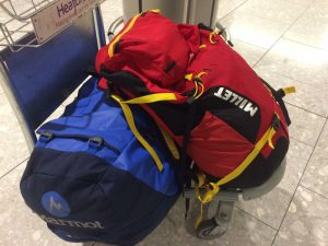 Red Millet rucksack leaning against a blue Adventure Peaks Mammut duffle bag at Heathrow check in