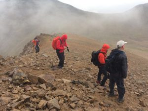 Group of climbers on acclimatisation walk up to 3200m with mist blowing in