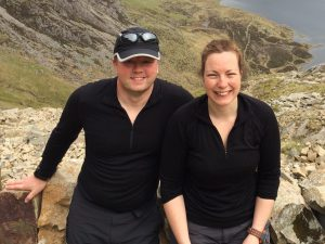 Michael and Paula Goude, owners of RockRiver Expeditions wearing Icebreaker merino base layers on a hike in Snowdonia with a lake in the background