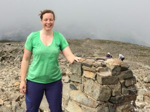 Paula Goude of RockRiver Expeditions stands at the trig point on the top of Scafell Pike