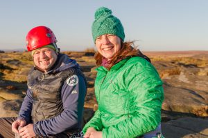 Paula Goude from RockRiver Expeditions wears a green Patagonia insulating jacket on a crag in the Peak District