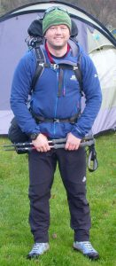 Mike Goude from RockRiver Expeditions stands in front of a tent in Scotland