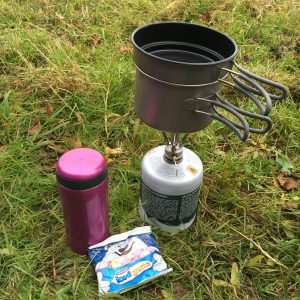 Pink Lifeventure thermal mug with MSR pocket rocket stove, colemans gas canister and ice gems on grass
