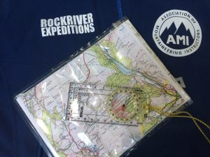 A blue jacket with a RockRiver Expeditions logo and an AMI logo (Association of Mountain Instructors) with a map and a Silva Expedition 4 compass