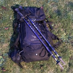 Leki Makalu walking poles leaning against a black Osprey rucksack