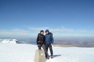 Michael and Paula Goude from RockRiver Expeditions stood at the trig point on the top of Ben Nevis, Scotland in the snow