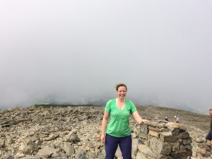 Paula Goude from RockRiver Expeditions at the trig point on Scafell Pike, Lake District with a backdrop of fog