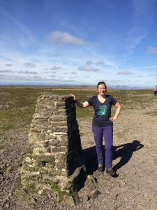 Paula Goude from RockRiver Expeditions at the trig point on Ingleborough the third peak in the Yorkshire Three Peaks Challenge